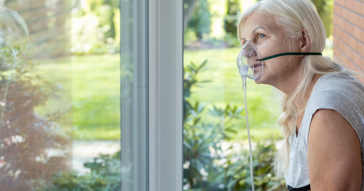 Woman with oxygen mask looking out window